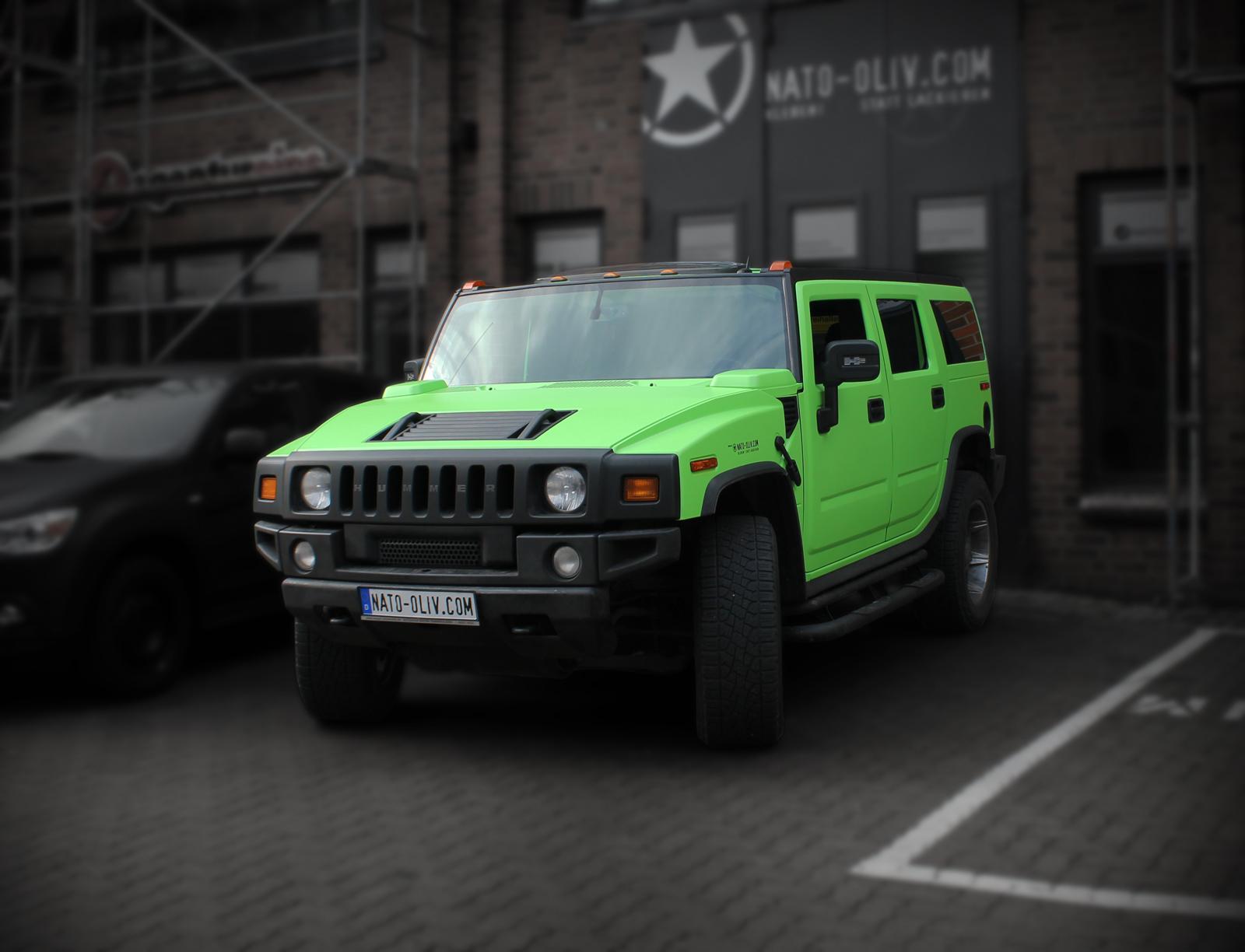 Ein mit grüner Folie beklebter Hummer H2, der Vor dem Tor von Nato-Oliv steht