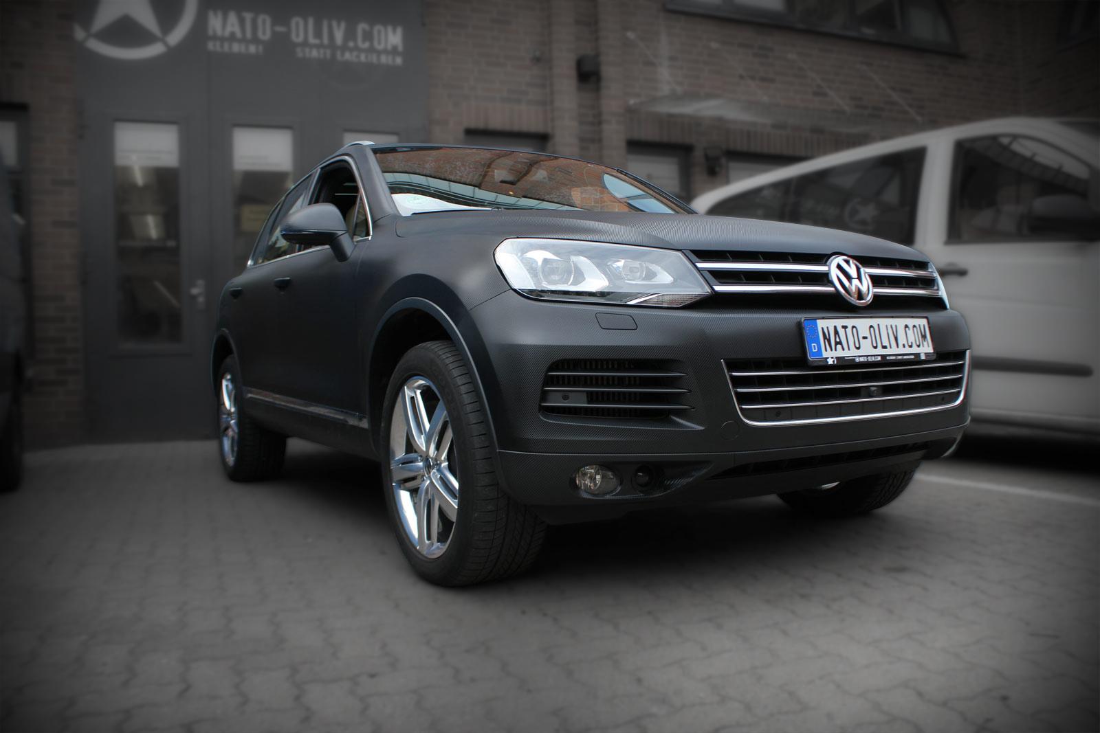 Zu sehen ist ein VW Touareg, der durch Vollverklebung mit einer Hochleistungsfolie eine optische Veredelung bekommen hat. Ursprünglich in einem braun metallic lackiert, danach mit Folie beklebt, ist dieser Wagen nun in schwarzer Carbon-Optik kaum wiederzuerkennen.