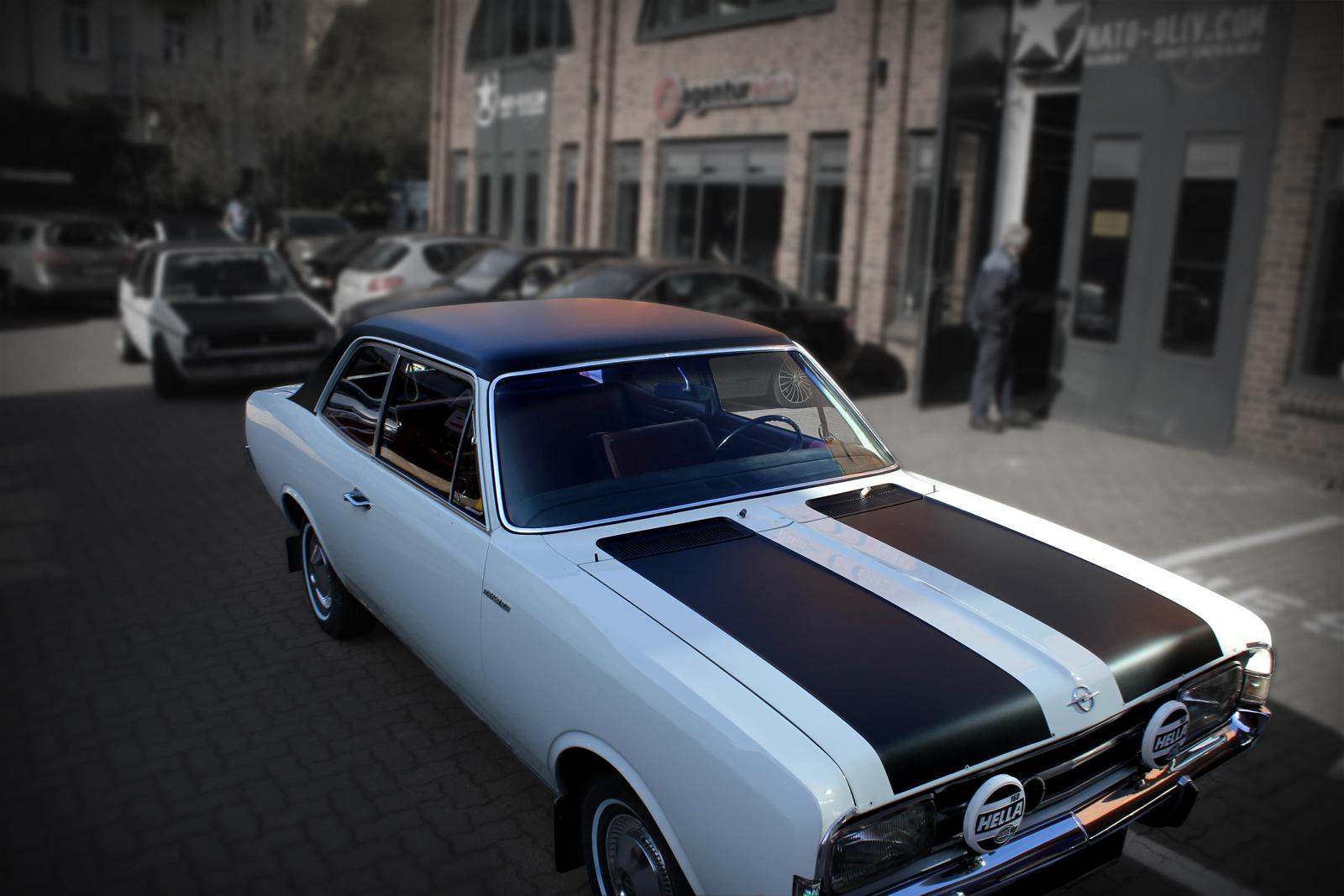 weiß glänzender Opel Rekord mit schwarz matter Teilfolierung auf dem Dach und Rallyestreifen auf der Motorhaube