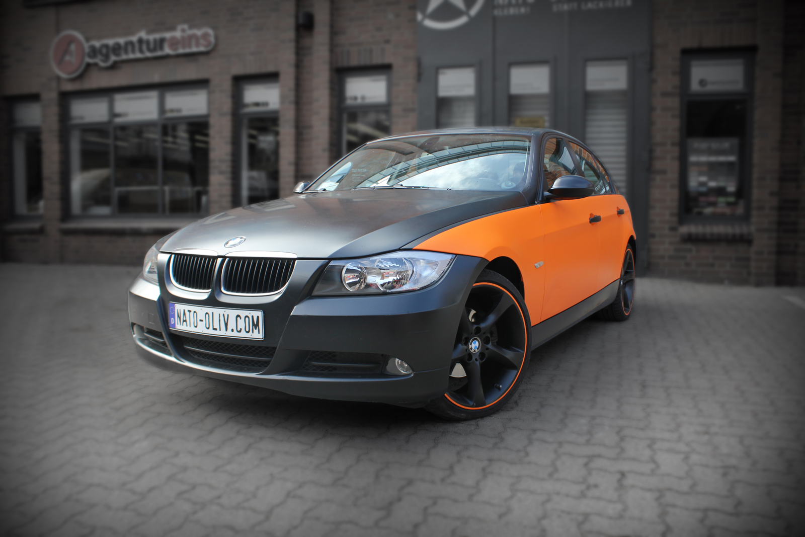 schräge Frontansicht eines 3er BMW's mit Teilfolierung in orange matt