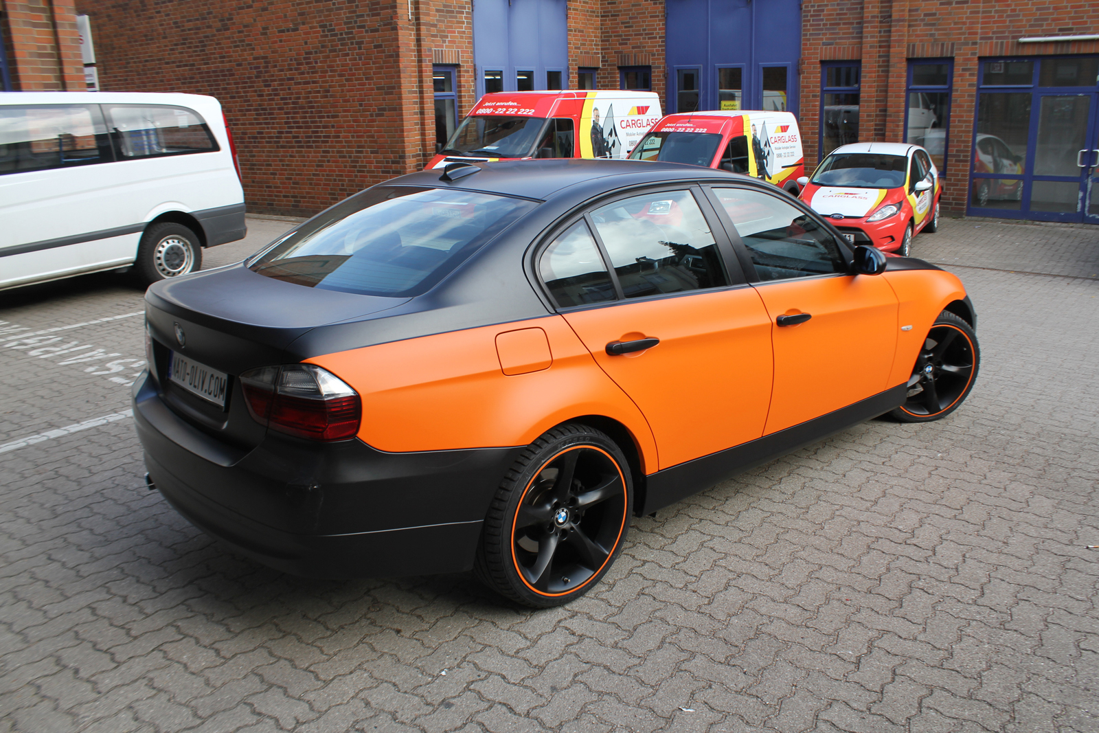 schräge Heckansicht eines 3er BMW's mit Teilfolierung in orange matt