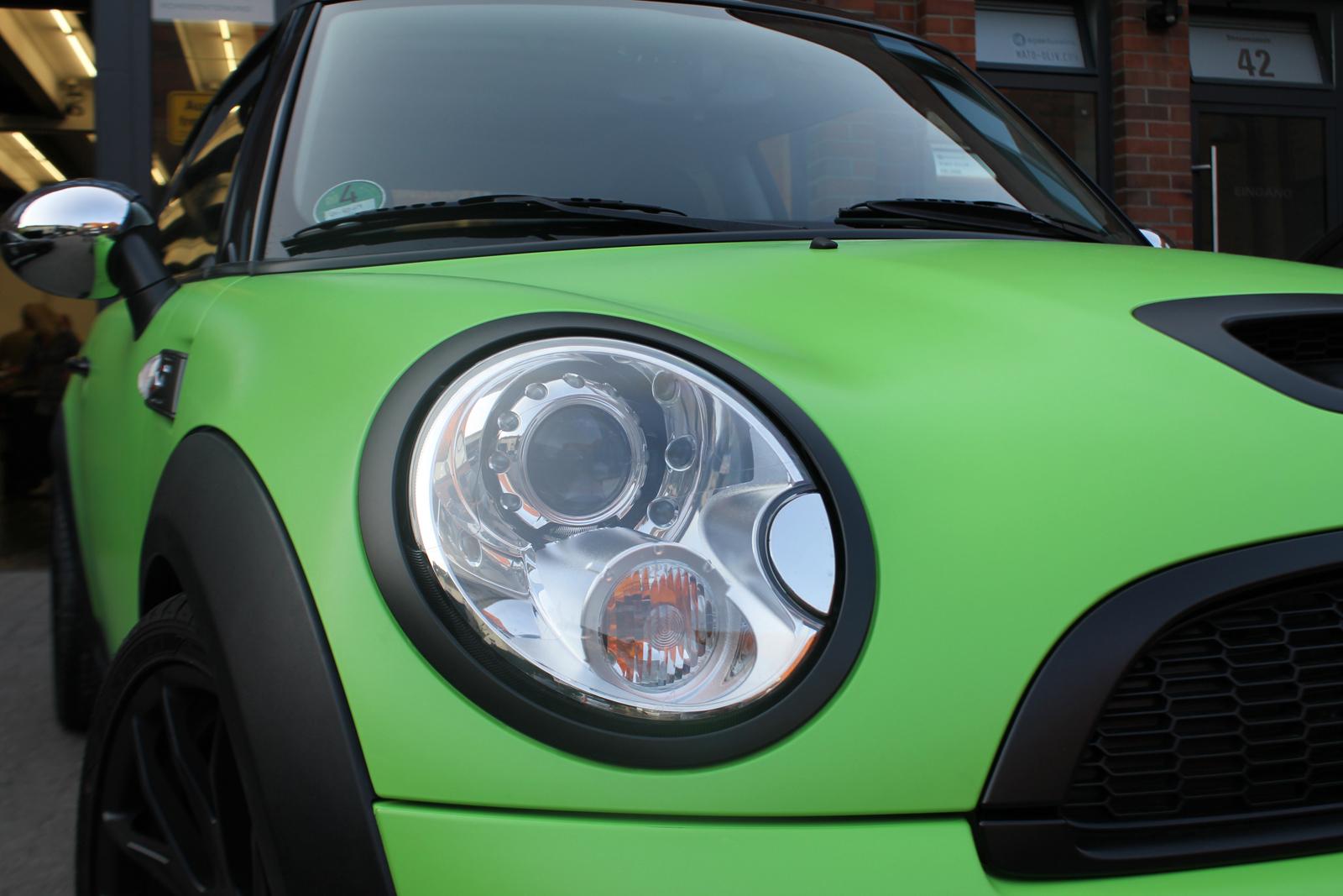 Frontansicht des giftgruen folierten Mini Coopers mit schwarz matter Beklebung des Scheinwerferrahmens