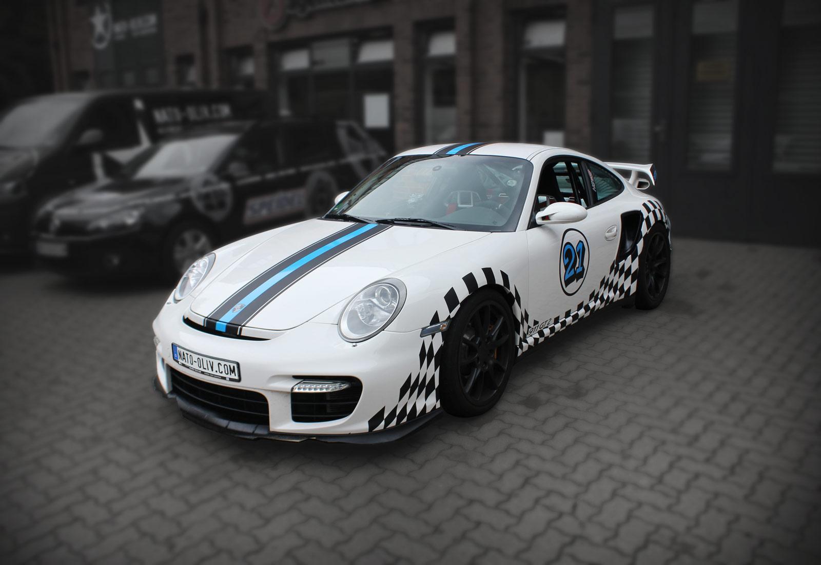 Porsche GT2 mit schwarz/blauem Rallyestreifen und Racing-Flaggen Design.