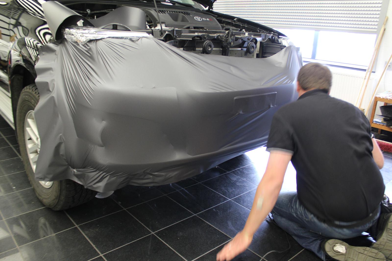 Beklebebung der Frontstoßstange eines Toyota Hilux mit Folie in anthrazit metallic matt