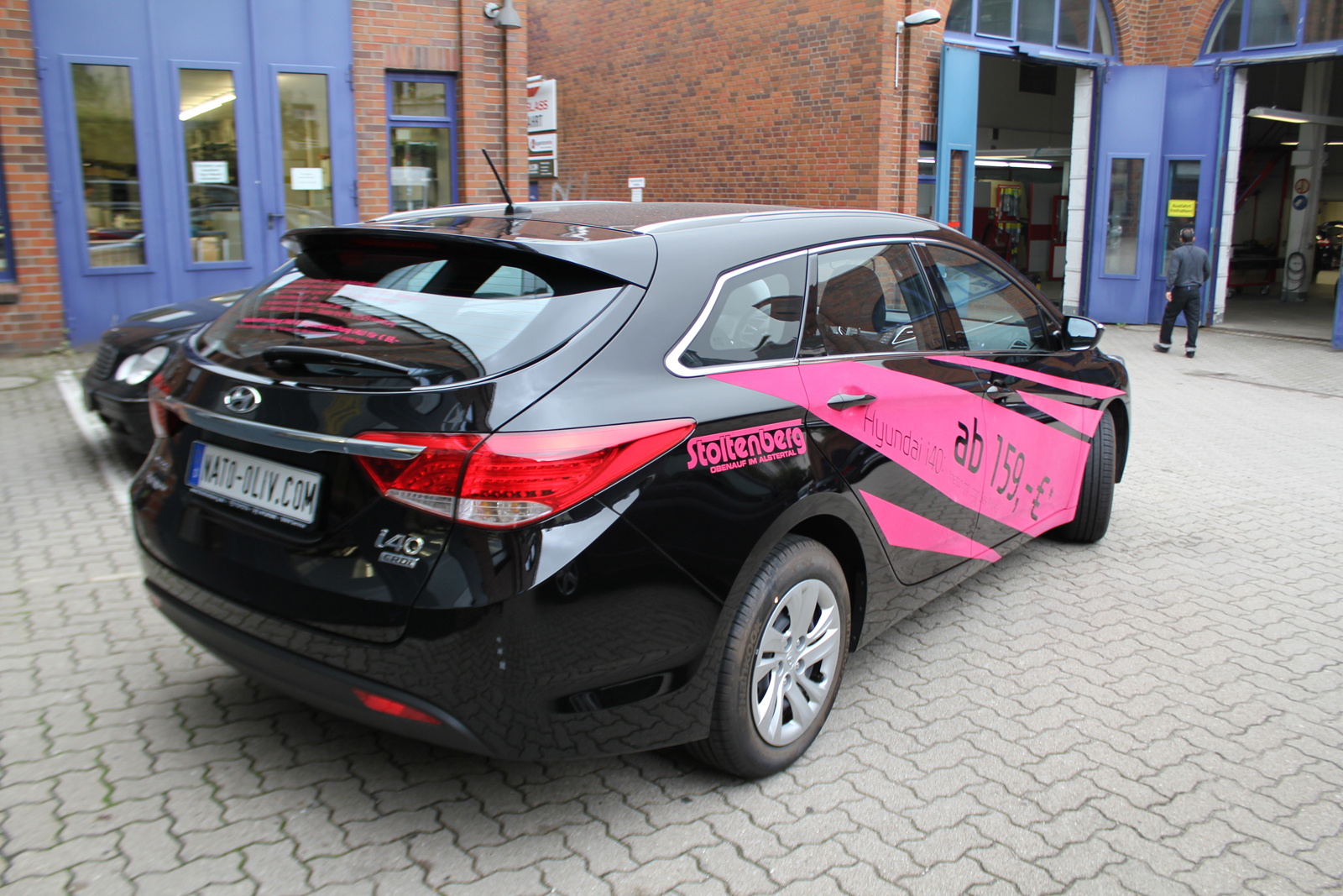 schraege Heckansicht des mit Samt-Pink-Folie beschrifteten Hyundai i40