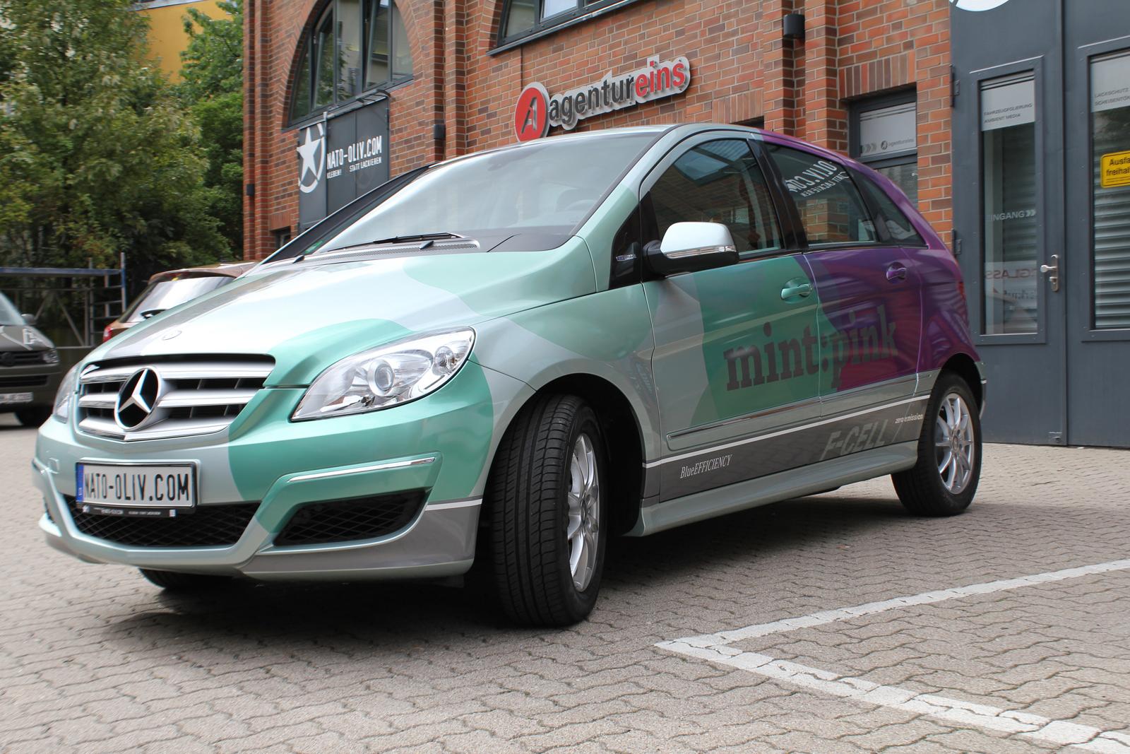 schraege Seitenansicht der Mercedes F-Cell B-Klasse mit Folierung in Mintgruen-metallic und Pink-metallic