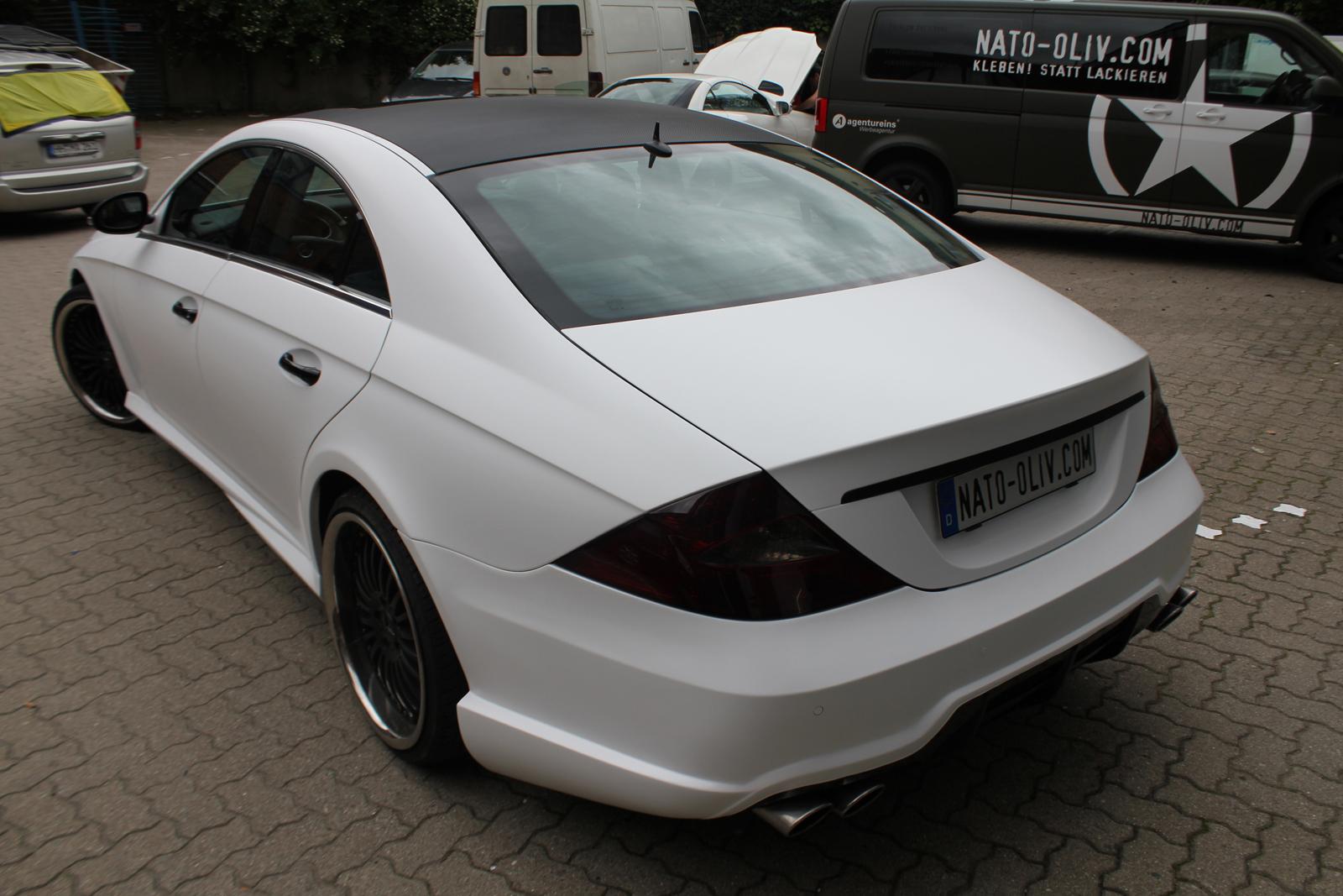 schraege Heckansicht des mit weiss matter Folie beklebten Mercedes CLS