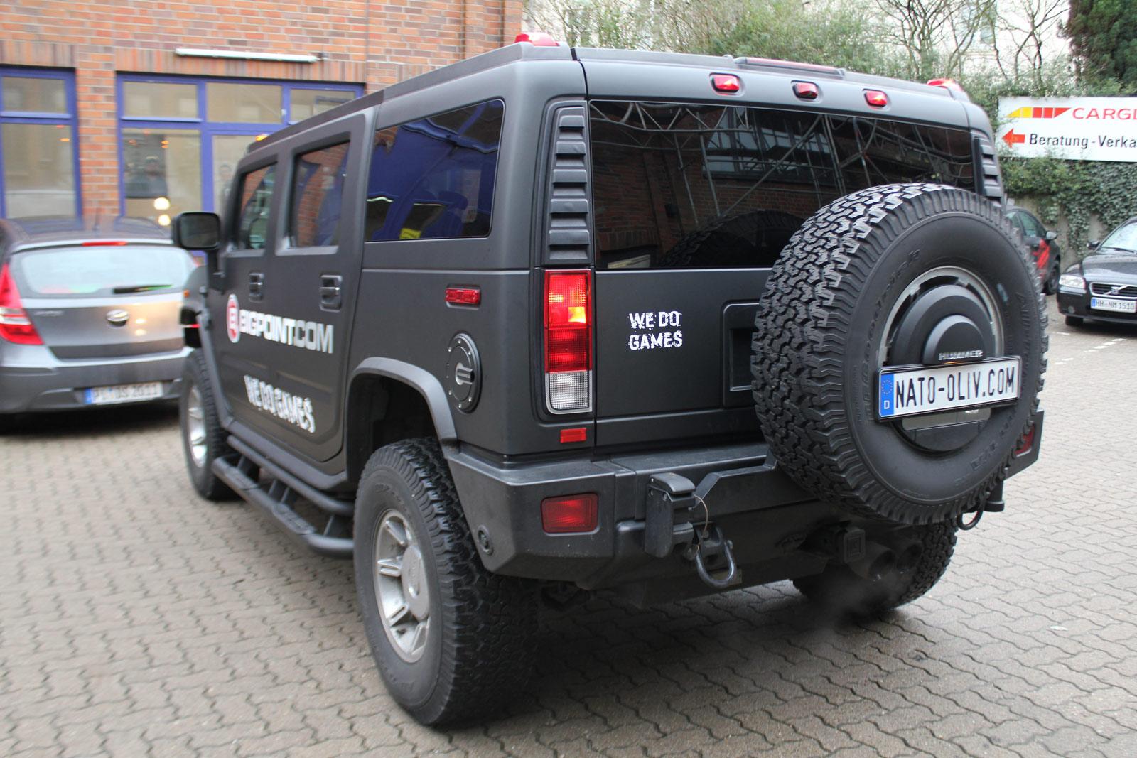 schraege Heckansicht des Hummer H2 mit Folierung in schwarz matt und Firmenlogo als Brandings