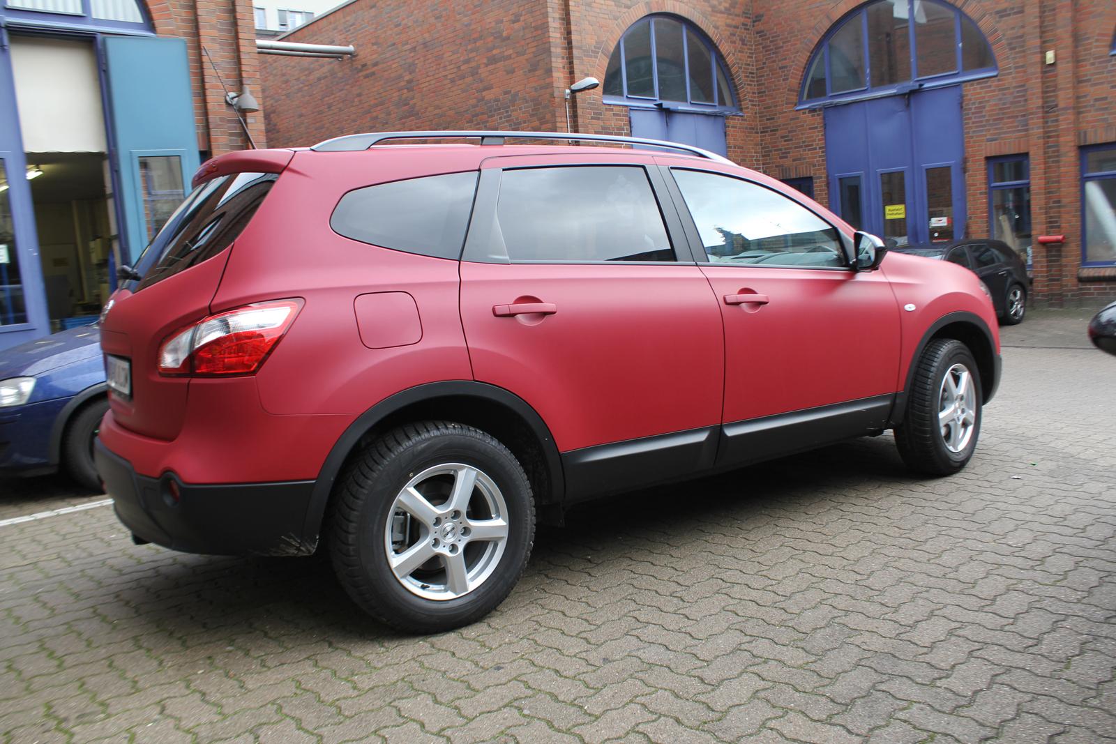 schraege Seitenansicht des Nissan Qashqai mit Garnet Red metallic matt Folie beklebt