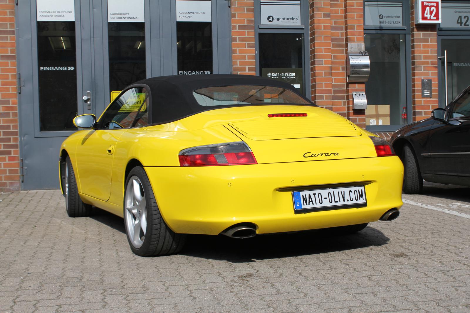 schraege Heckansicht des mit Folie in Gelb Glanz beklebten Porsche 911 Cabrio