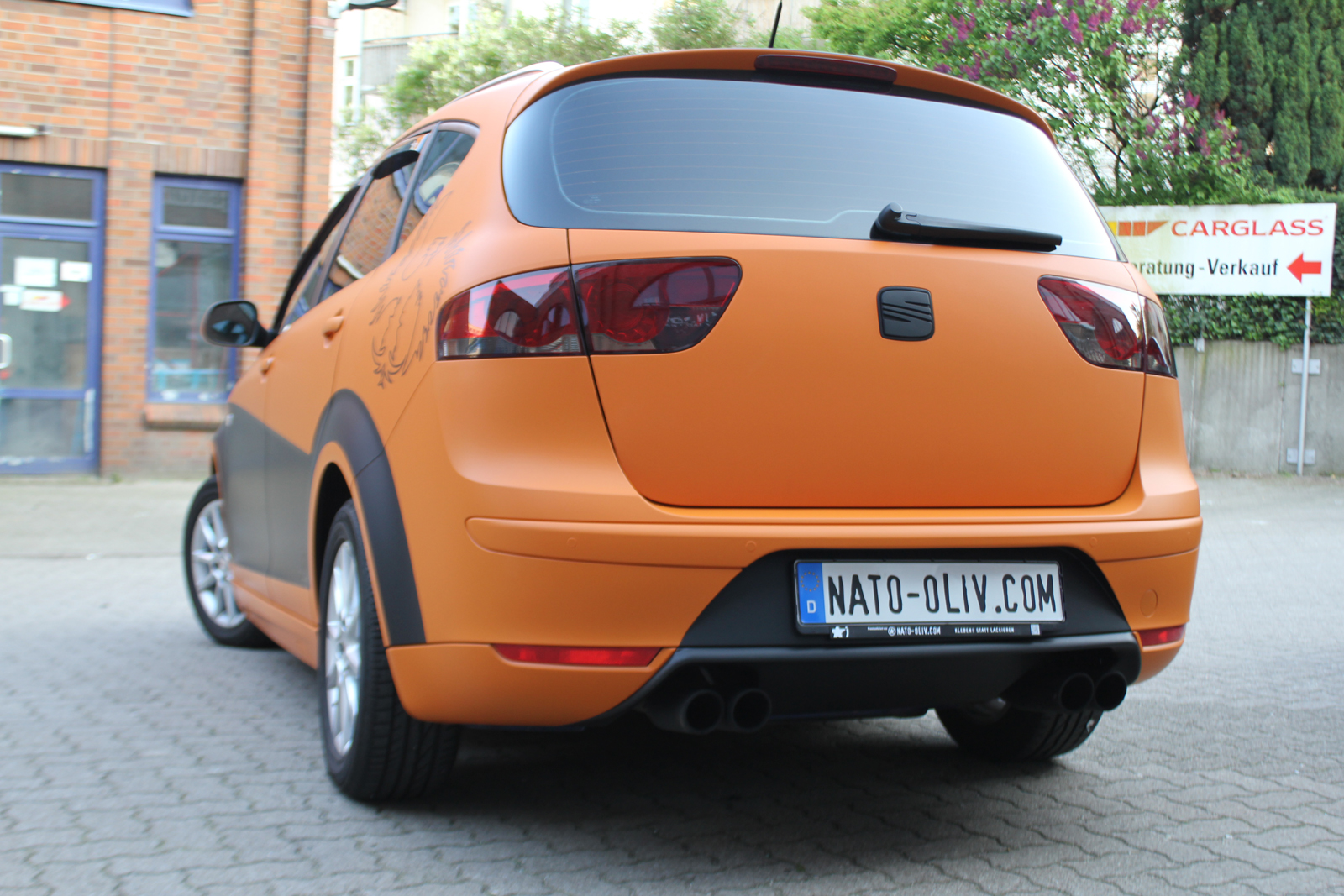 schraege Heckansicht des Seat Altea XL in orange matt und schwarz matt mit Folie beklebt