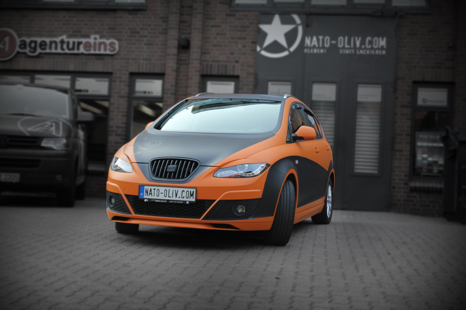 schraege Frontalansicht des Seat Altea XL in orange matt und schwarz matt mit Folie beklebt
