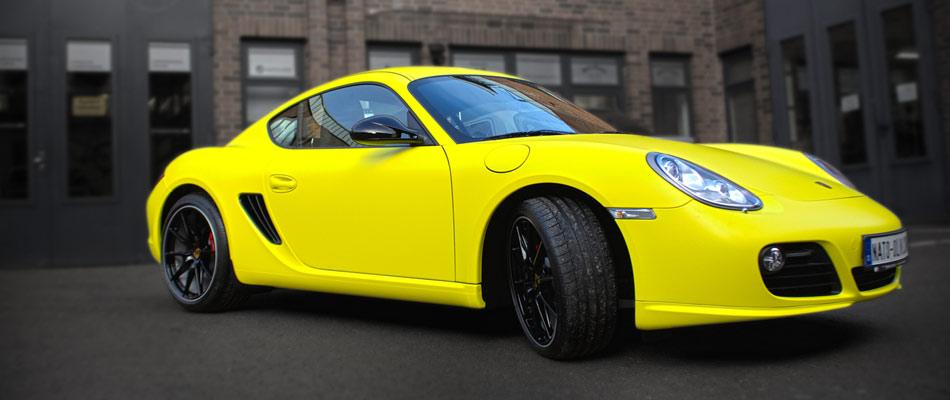 Porsche Cayman Folierung komplett in gelb matt mit Details in Carbonfolie.