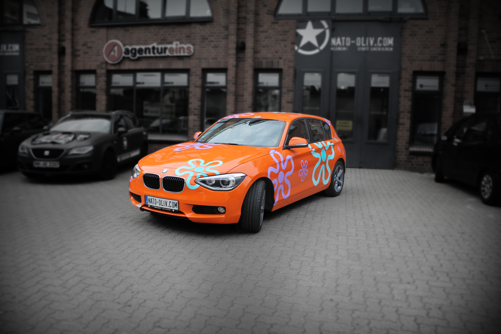 Car Wrapping BMW 1er mit Folie in Orange und Blumen in türkis und lila
